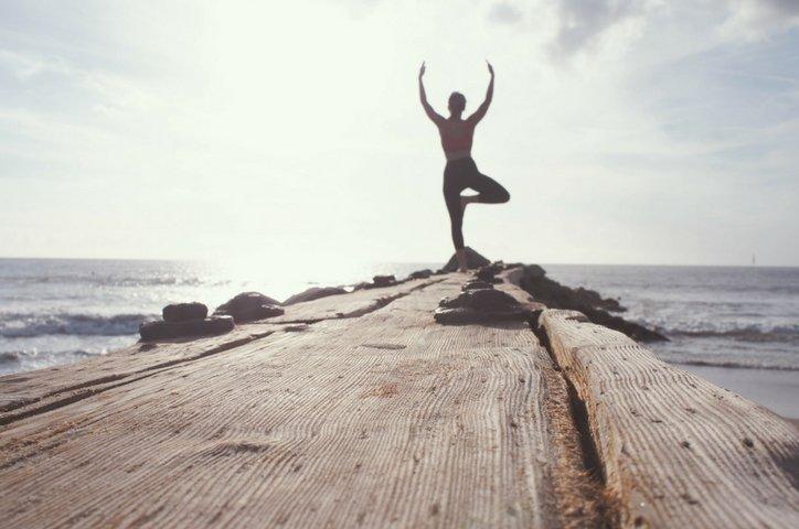 Foto de una chica en la playa haciendo yoga